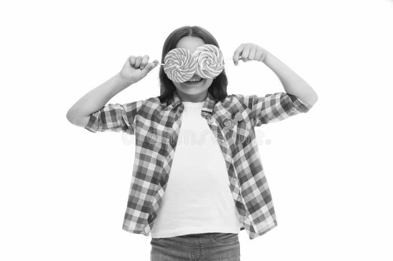 Девушка ребенка с предпосылкой красочных конфет леденцов на палочке белой Девушка счастливая с глазами конфеты Улыбка маленького  стоковое изображение