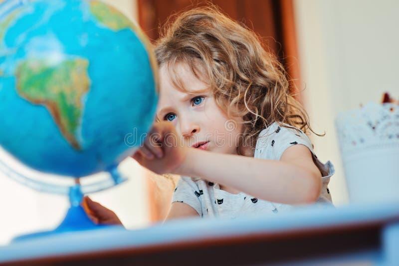Девушка ребенка уча с глобусом дома стоковая фотография