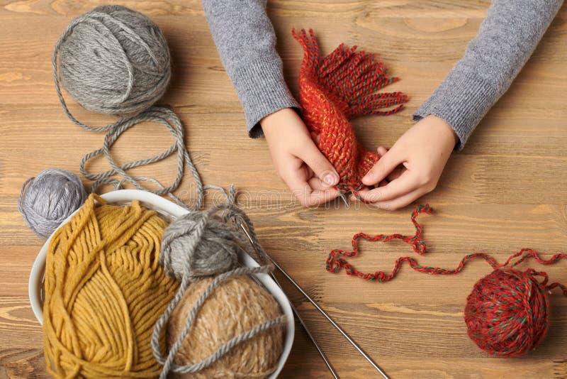 Девушка ребенка учит связать Красочные пряжи шерстей на деревянном столе Крупный план руки стоковое фото