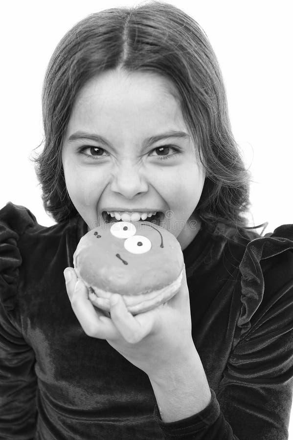 Девушка ребенк голодная для сладкого донута Донут будет настолько популярным Уровни сахара и здоровое питание Счастливое детство  стоковая фотография