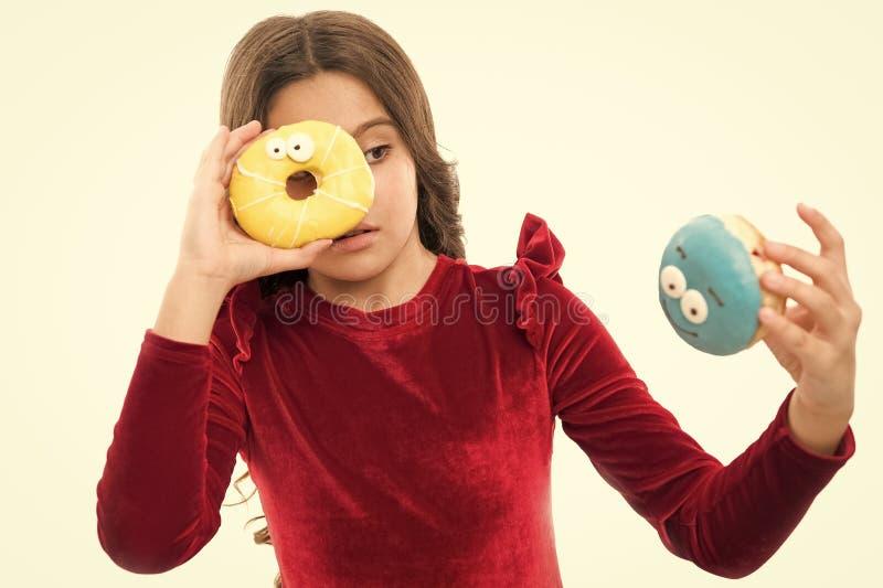 Девушка ребенк голодная для сладкого донута Уровни сахара и здоровое питание Донут ее сладкая одержимость Счастливое детство и стоковая фотография rf