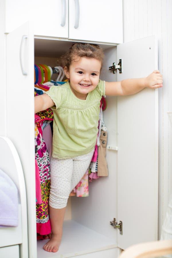 Девушка ребенк играя и пряча внутренний шкаф стоковые фотографии rf