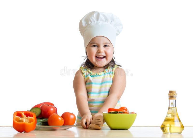Девушка ребенк кашевара подготавливая овощи стоковое фото rf