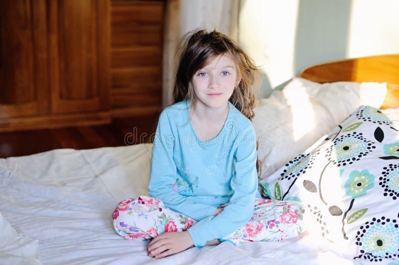 Девушка ребенк на кровати в спальне стоковые изображения