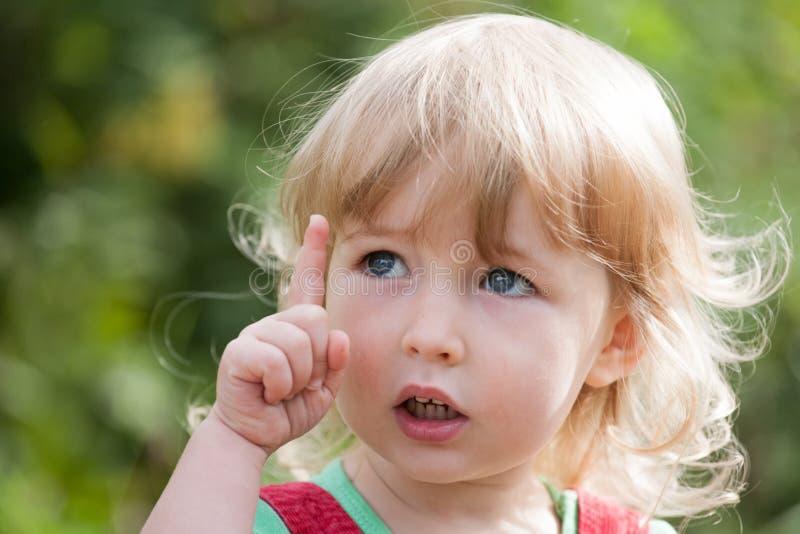 Девушка ребенк с forefinger вверх стоковые фото
