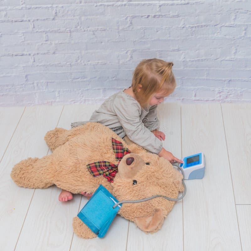 Девушка, ребенок измеряет давление медведя игрушки, доктора игр стоковые изображения