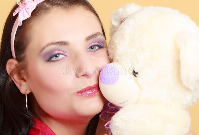 Девушка ребяческой молодой женщины ребячья в розовой целуя игрушке плюшевого медвежонка стоковое изображение