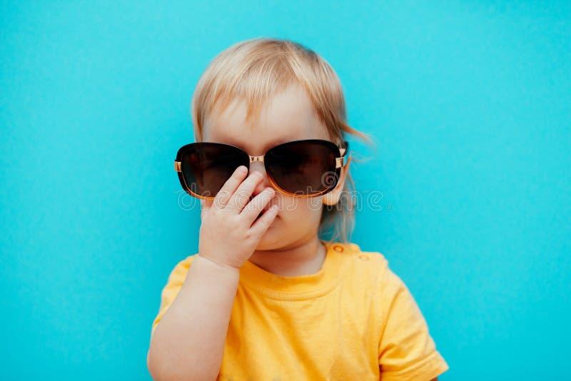 Девушка регулирует ее солнечные очки на мосте вашего носа стоковое изображение