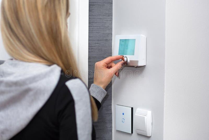 Девушка регулирует и регулирует комнатную температуру на умном переключателе стоковые изображения