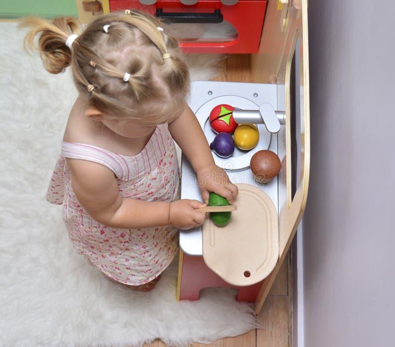 девушка режет деревянные овощи на кухне игрушки стоковое изображение