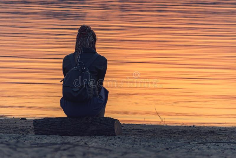 Девушка рекой на заходе солнца стоковая фотография rf
