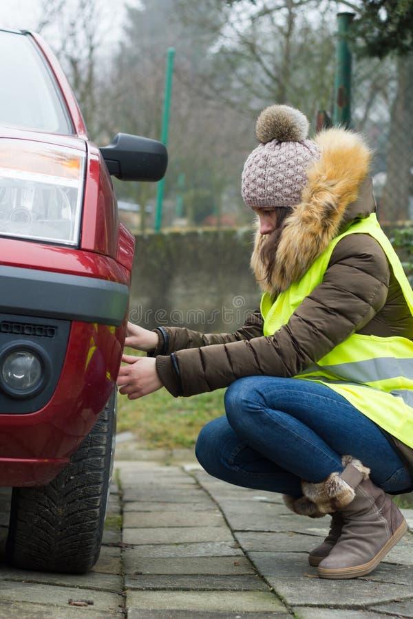 Девушка ремонтируя сломленный автомобиль дорогой; смотреть уныла и утомлена стоковые изображения