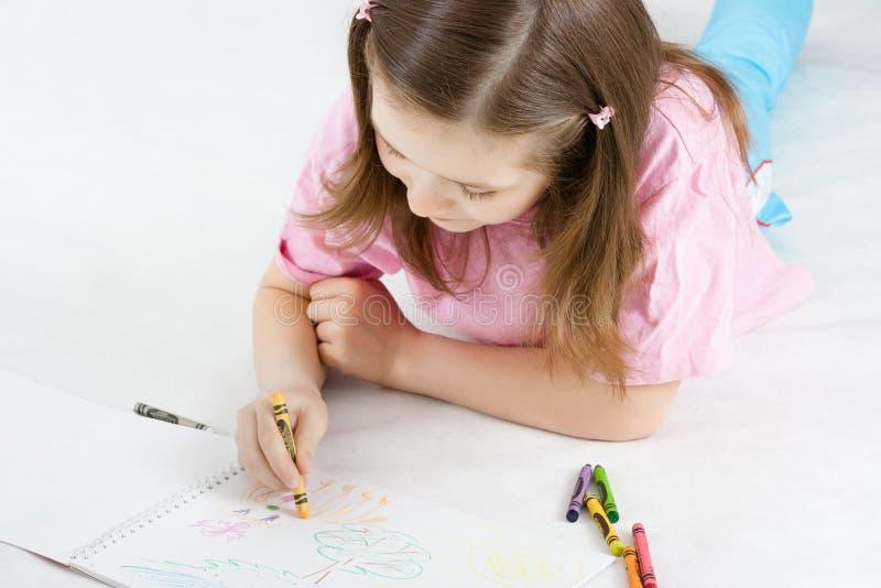 Девушка рисует лежать на поле стоковая фотография