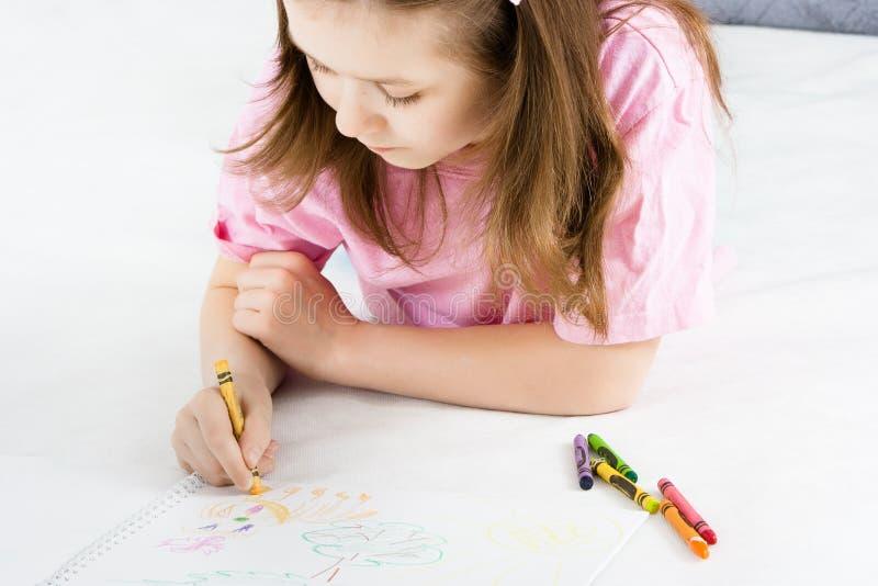 Девушка рисует лежать на поле стоковое изображение