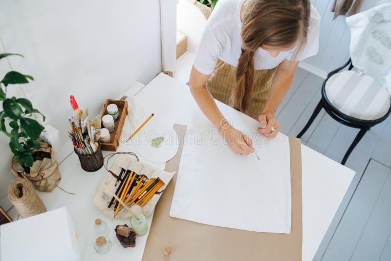 Девушка рисует за столом в творческом мастер-классе стоковая фотография rf