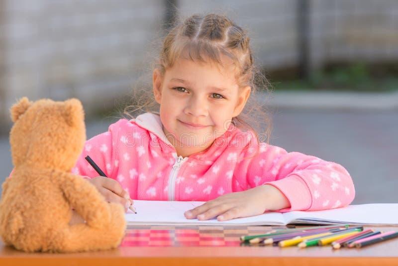 Девушка рисует с crayons и улыбка, он посмотрел стоковое изображение rf