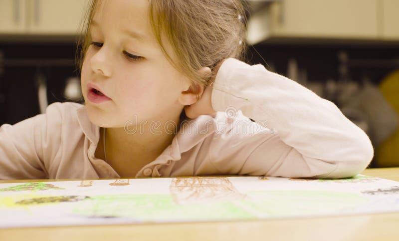 Девушка рисуя пастельные crayons на бумаге на таблице стоковая фотография