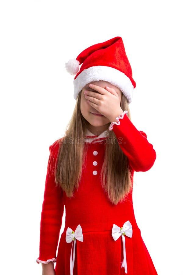 Девушка рождества с закрыла глаза с ее рукой, нося шляпу santa изолированную над белой предпосылкой стоковые изображения
