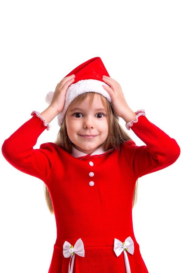 Девушка рождества Puzzled усмехаясь нося шляпу santa изолированную над белой предпосылкой, держа ее руки на голове стоковое фото rf