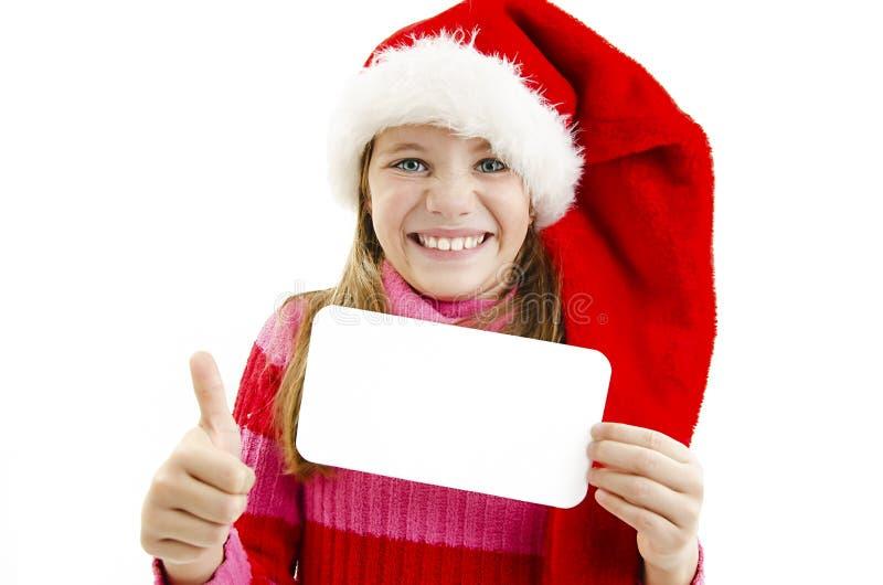 Девушка Санта представляя карточку и давая о'кей для его стоковые фото