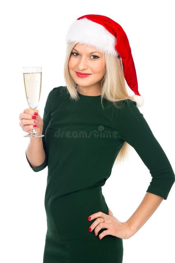 Девушка Санты в зеленом платье усмехаясь с стеклом шампанского стоковое фото