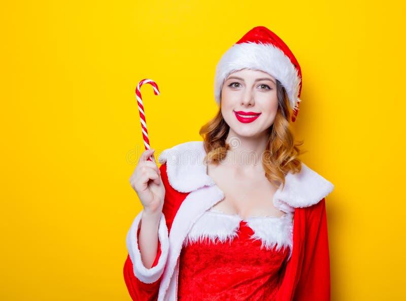 Девушка Санты Clous в красных одеждах с конфетой стоковые фото