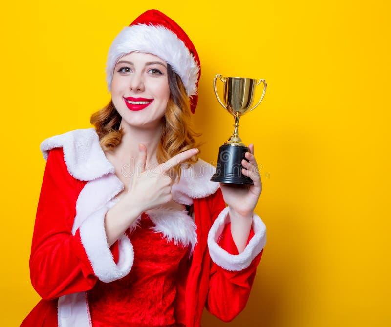 Девушка Санты Clous в красных одеждах с призом трофея стоковые изображения