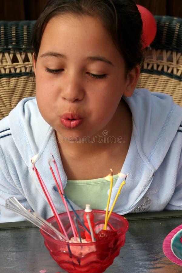девушка свечек дня рождения дуя вне стоковое фото