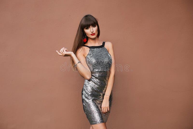 Девушка сексуального брюнета модельная с идеальным телом в серебряном платье коктейля стоковое изображение