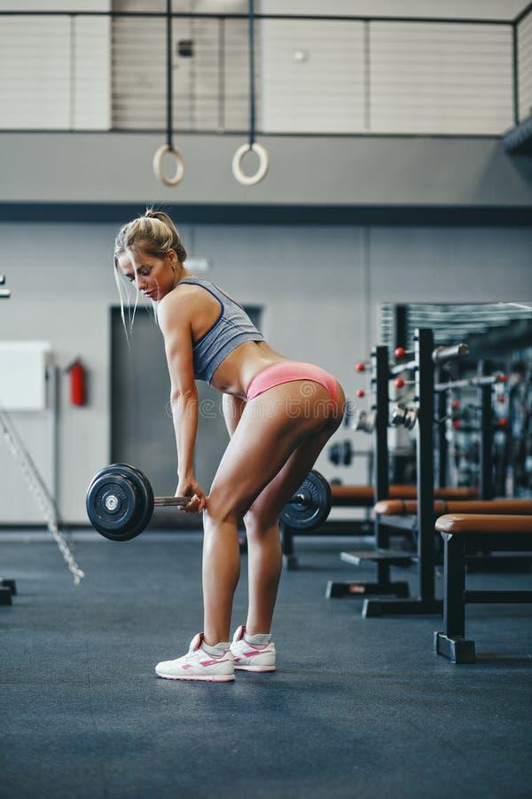 Девушка сексуального фитнеса счастливая белокурая в носке спорта с совершенным телом в спортзале представляя и усмехаясь стоковые фотографии rf