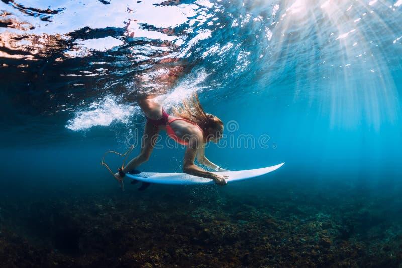 Девушка серфера в бикини с пикированием surfboard подводным с нижней океанской волной бочонка стоковые фотографии rf