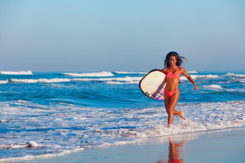 Девушка серфера в бикини с surfboard бежит вдоль пляжа океана стоковые изображения