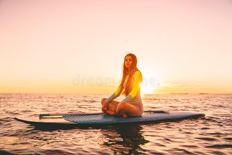Девушка серфера дальше стоит вверх доска затвора, тихое море с теплыми цветами захода солнца стоковые изображения rf