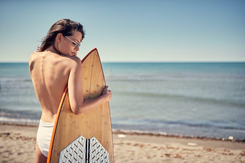 Девушка серфера Красивая сексуальная женщина на пляже - задний взгляд стоковое фото