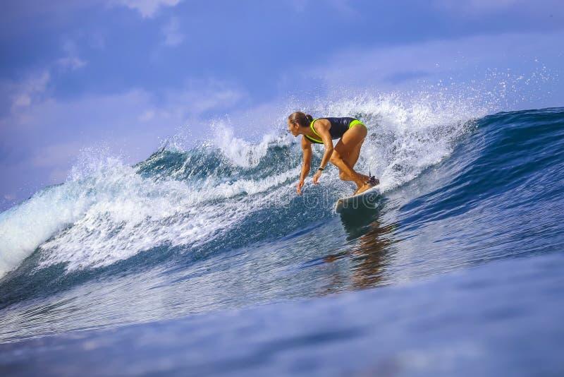 Девушка серфера на изумительной голубой волне стоковое фото