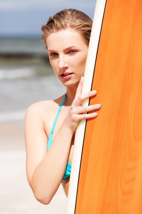 Девушка серфера на пляже в бикини стоковое изображение rf