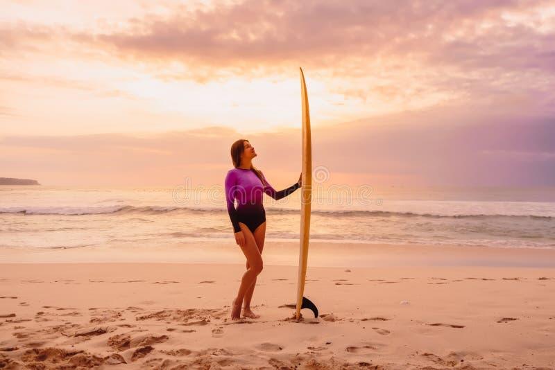 Девушка серфера представляя с surfboard на пляже со светом захода солнца стоковое изображение rf
