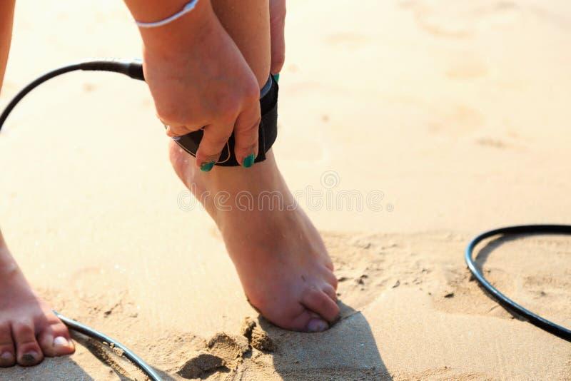 Девушка серфера прикрепляет поводок к ноге стоковая фотография rf
