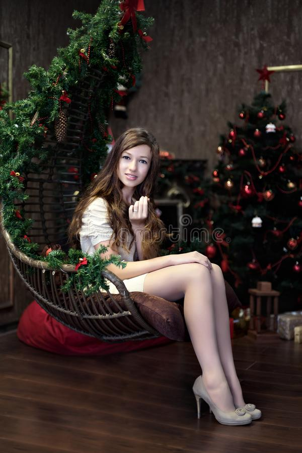 Девушка сидит бесполезное ослабляет в салоне во время торжества рождества и Нового Года с рождественской елкой стоковое фото