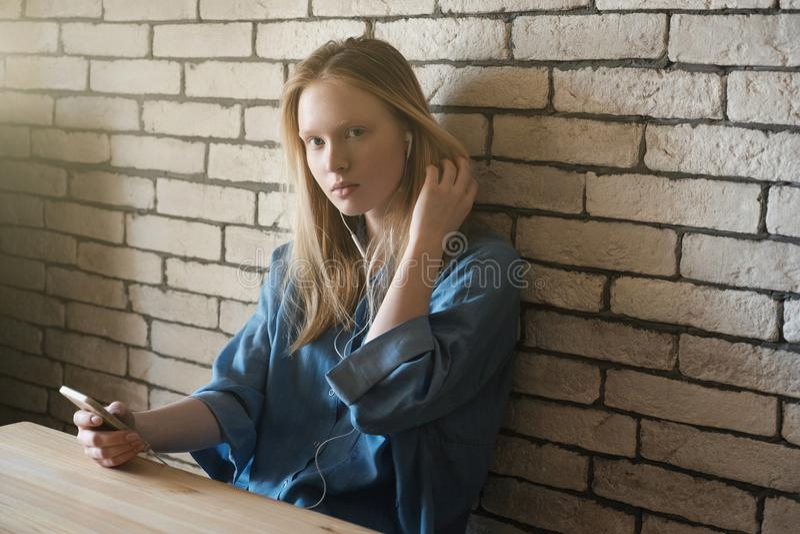 Девушка сидит в наушниках полагаясь против стены, смотря внутри стоковые изображения rf