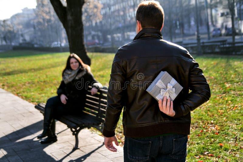 Девушка сидит в парке, парне причаливая с подарком стоковая фотография rf