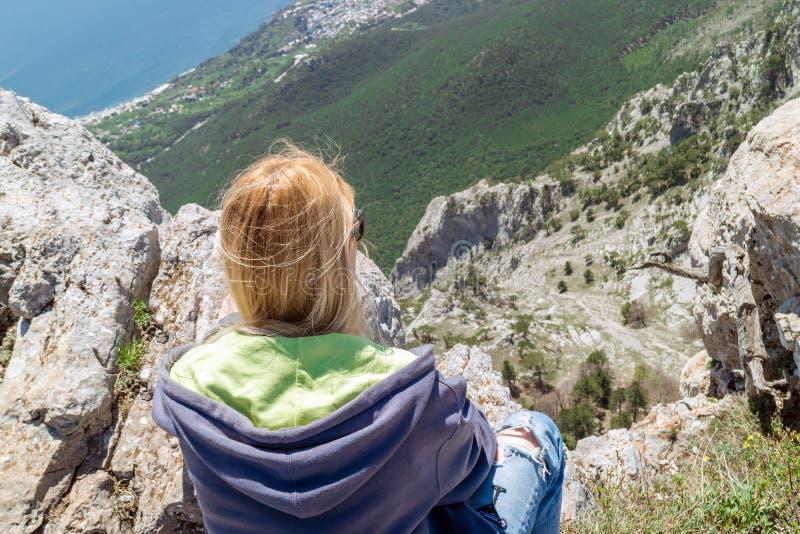 Девушка сидит на краю скалы и смотрит вниз стоковая фотография