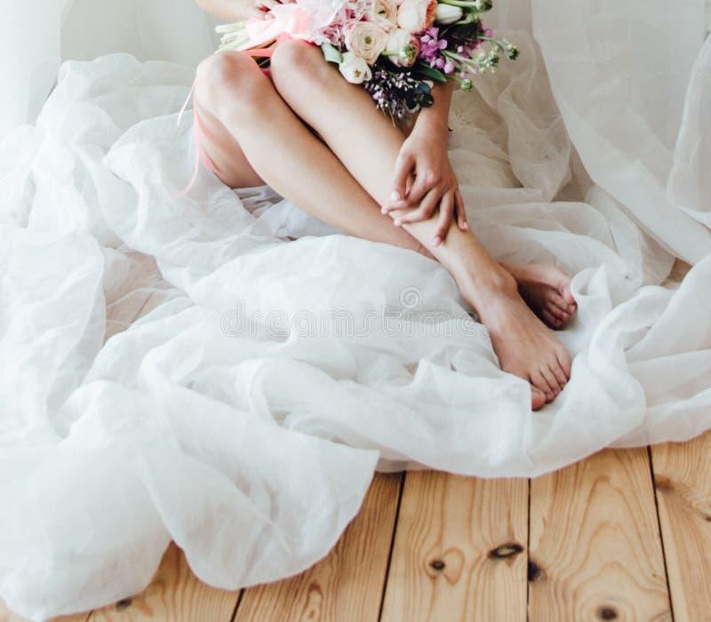 Девушка сидит на поле и держит букет свадьбы на ее коленях стоковые фотографии rf