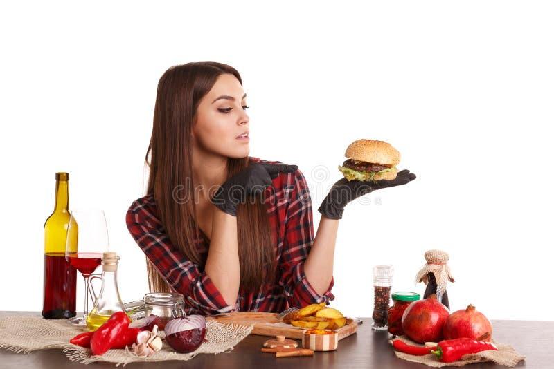 Девушка, сидит на таблице с едой, держит бургер и пункты на ей с пальцем белизна изолированная предпосылкой стоковое изображение