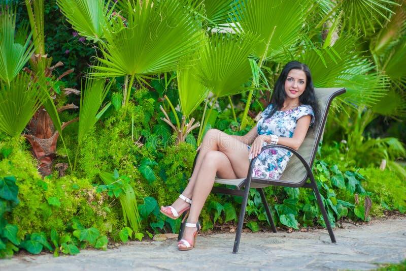 Девушка сидит около листьев ладони Красивый брюнет в платье сидит на стуле около растительности, отдыхая в стоковое фото rf