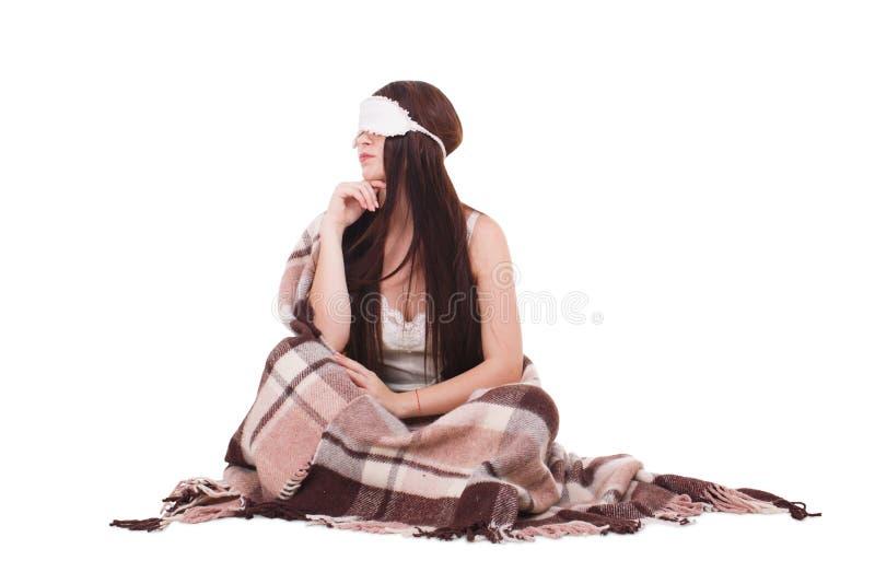 Девушка, сидит с маской для спать и покрыла теплый половик На белой предпосылке стоковая фотография