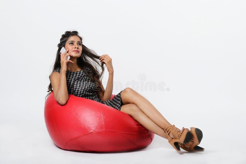 Девушка сидит o кресло сумки фасоли с говорить на телефоне стоковые изображения rf