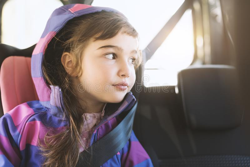 Девушка сидя в автомобиле и смотря вне из окна автомобиля стоковые фотографии rf