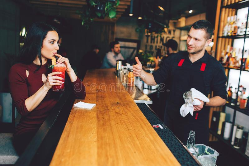 Девушка сидя в баре и выпивая коктеиле который она приказала Она любит она Бармен счастлив его клиент удовлетворен стоковое изображение