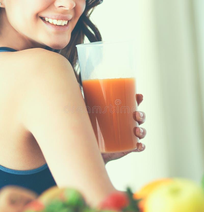 Девушка сидя в кухне на столе с плодом и соком стекел стоковое фото rf